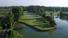 Aerial rising shot of a golf course hole with pond Stock Footage