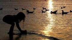 The Little Girl Played on the Beach. She is Gaining in a Bucket of Water in Stock Footage
