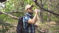 Lost tourist man close-up walking through the forest drinks water. man with b Stock Footage