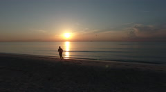 Silhouette of male jogger on beach running towrards the sun at sunrise Stock Footage
