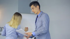 Male is presenting working plan with female assistant Stock Footage