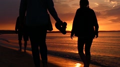 Family Walking on the Shore at Sunset. Slow Motion. Stock Footage