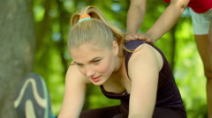 Woman stretching outdoor. Sporty girl help to do stretching exercises Stock Footage