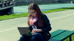 Absorbed girl sitting on the bench and typing something on laptop Stock Footage