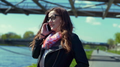Pretty girl chatting on cellphone on pathway and going somewhere Stock Footage