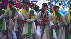 Line of men in traditional clothing dance in line during a Hindu festival. Stock Footage