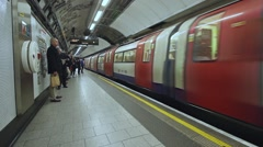 LONDON  U.K.- CIRCA 2016 - Tube underground subway train arrives, wide shot, Stock Footage