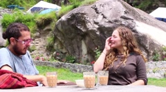 Two friends, man and woman, sip tea, talk and laugh at cafe in the Himalayas. Stock Footage