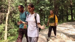 Three hikers- man and two women-walk a beautiful Himalayan path. Moving shot Stock Footage