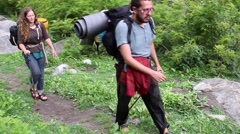 Two friends, man and woman, hike with camping backpacks along path in Himalayas Arkistovideo