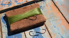 A fishing line of nylon wrapped on a cork with three fishing hooks Stock Footage