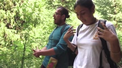 Young woman speaks to man as they walk a beautiful forest path. Moving shot Stock Footage