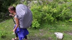 Two women hike with camping backpacks passing camera in Himalayas Arkistovideo