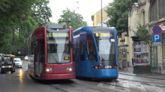 2 tramways (1 blue, 1 red) pass each other at station in krakow street, Poland Stock Footage