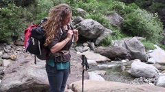 Young woman by river puts on large camping backpacks and heads off on a trek Stock Footage