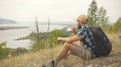 Tourist man close-up sitting the mountain drinks water. men with backpack in Stock Footage