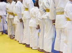 Group of children in kimono standing on tatami on martial arts training Stock Photos