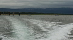 POV-Wake from fishing boat leaving dock on overcast day Stock Footage