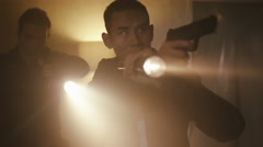 4K Police detectives with handguns & flashlights investigating dark apartment. Stock Footage