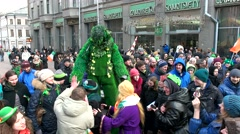 People on the street in extravagant costumes, a huge green man Stock Footage