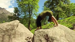 Young woman does fish yoga pose in slow motion, before mountain vista Stock Footage