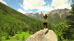 Young woman raises hands in an expression of freedom before mountains Stock Footage
