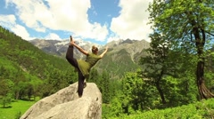Young woman does stretching yoga poses in slow motion, before mountain vista Stock Footage