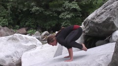 Young woman crouches and lifts, side view, yoga by mountain strem Stock Footage