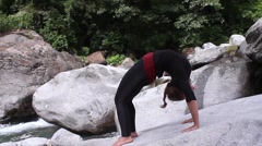 Young woman arches back and strteches leg, yoga pose by mountain stream Stock Footage