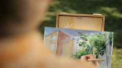 Artist painting a house and a tree from nature. Plein air Stock Footage