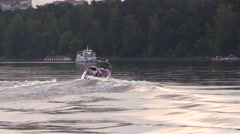 Boat float and drag water-skier by the river Stock Footage