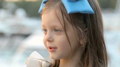Portrait of a little girl three years with the blue bow on her head, stands near Stock Footage