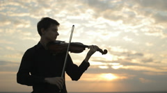 A young violinist in a black shirt, playing on the roof Stock Footage