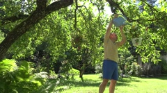 Gardener man with watering can water flower pots hanging on fruit tree in summer Stock Footage