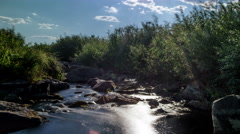 Stream running through the stones. Moving clouds Stock Footage