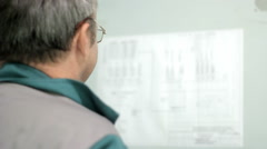 A technician looks at a drawing. Electric wiring diagram looks networks Stock Footage
