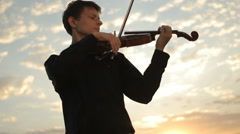 Violinist plays against the sunset. Violin on sunset Stock Footage