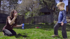 Mother blows bubbles for son Stock Footage