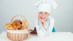 Portrait little baker near her basket of bread and smiling at camera isolated Stock Footage