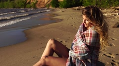 Young beautiful girl sitting on the river side sheltered plaid enjoying sunset Stock Footage