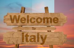 Welcome to Italy sing on wood background with blending national flag Stock Photos