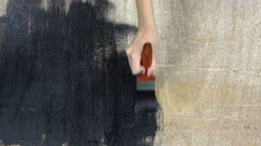 Hand holding a brush applying black paint on a wooden surface. Stock Footage