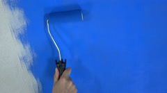 Hand holds the roller and paints the wall of blue paint. Stock Footage