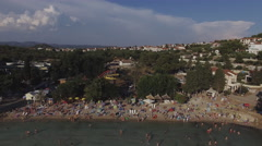 People on the beach relaxing and swimming in the Adriatic Sea. Aerial view 4K Stock Footage