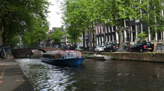 Amsterdam residential canal tourist boat  summer Holland Stock Footage