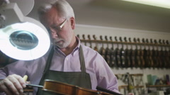 4K Craftsman in his workshop, making and restoring violins Stock Footage