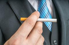 Man holds tobacco cigarette in hand. Stock Photos