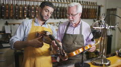 4K Portrait of happy smiling violin makers in their workshop Stock Footage