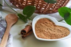 Powdered cinnamon in heart shaped bowl Stock Photos