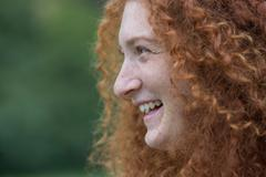 Cheerful young woman with freckles and red curly hair Stock Photos